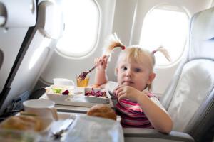 Bambina che mangia in aereo